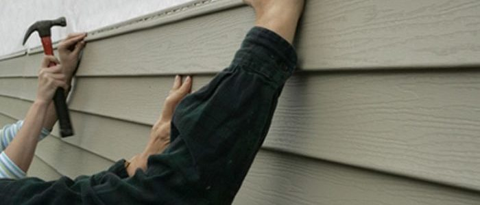 two people installing siding on a residential home