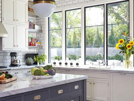A kitchen's new windows let the sun illuminate the space.