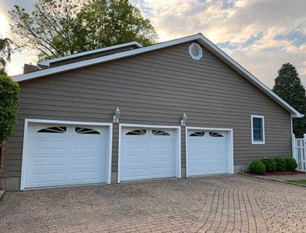 A three car garage with Everlast PVC siding