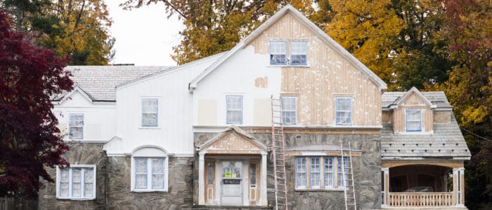 A home has ladders leaning against it, with half of the house having a fresh coat of white paint applied to it, while the other half is a faded brown color, waiting to be repainted.